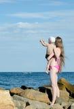 La mère et le fils sur les mains sont parmi les pierres sur le bord de mer, montrent dans la distance Photographie stock libre de droits
