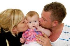 La mère et le père embrassent le bébé Photo stock