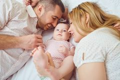 La mère et le père jouent avec le bébé sur le lit images stock