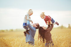 La mère et le père tient sur des mains leurs petits enfants sur un champ agricole Images libres de droits