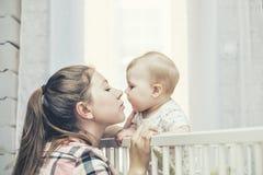 La mère et le petit bébé est dans la huche se sont réveillés pendant le matin et photo stock
