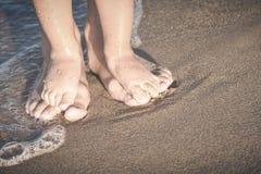 La mère et le petit bébé jouent sur une plage r Image stock