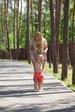 La mère et le petit fils jouent en parc d'été Images stock