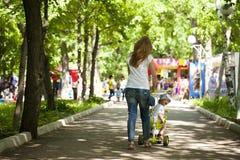 La mère et le petit fils jouent en parc d'été Photo stock
