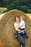 La mère et le petit fils sur le foin jaune mettent en place Image libre de droits