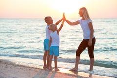 La mère et les enfants font des exercices sur la plage, ils rencontrent le lever de soleil Forme physique, sport, yoga et concept photographie stock libre de droits