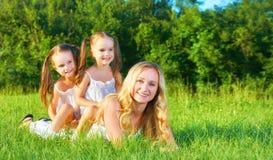 La mère et les enfants heureux de famille jumellent des soeurs sur le pré dans le summe Photographie stock