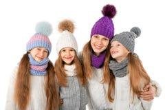 La mère et les enfants mignons en hiver chauffent des chapeaux et des écharpes sur le blanc Vêtements d'hiver d'enfants Photographie stock libre de droits