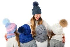 La mère et les enfants mignons en hiver chauffent des chapeaux et des écharpes sur le blanc Vêtements d'hiver d'enfants Photographie stock