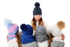 La mère et les enfants mignons en hiver chauffent des chapeaux et des écharpes sur le blanc Vêtements d'hiver d'enfants Image libre de droits