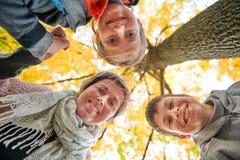 La mère et les enfants sont en parc de ville d'automne Ils sont des parents posant, souriant, jouant et ayant l'amusement Arbres  photo libre de droits
