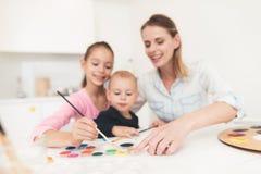 La mère et les enfants sont engagés dans le dessin Ils ont l'amusement dans la cuisine La fille tient son jeune frère dans elle Photo stock