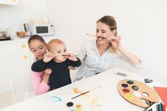 La mère et les enfants sont engagés dans le dessin Ils ont l'amusement dans la cuisine La fille tient son jeune frère dans elle Image stock