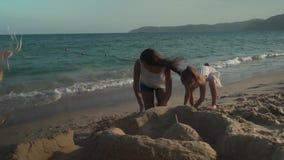 La mère et les filles heureuses construisent un château de sable sur la plage de la vidéo de longueur d'actions de mouvement lent clips vidéos