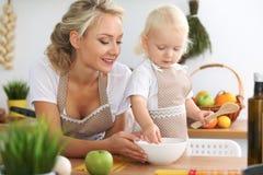 La mère et la petite fille font cuire dans la cuisine Passant le temps tout ensemble ou concept de la famille heureux Images libres de droits
