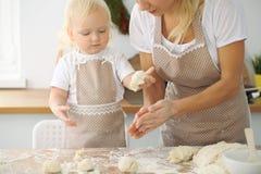 La mère et la petite fille font cuire dans la cuisine Passant le temps tout ensemble ou concept de la famille heureux Images stock