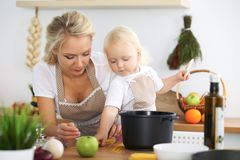 La mère et la petite fille font cuire dans la cuisine Passant le temps tout ensemble ou concept de la famille heureux Photo libre de droits