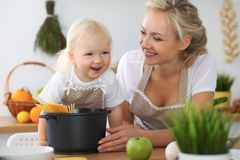 La mère et la petite fille font cuire dans la cuisine Passant le temps tout ensemble ou concept de la famille heureux Image libre de droits