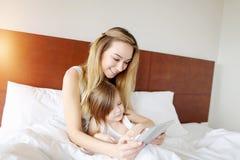 La mère et la petite fille utilisent le comprimé au lit blanc avec le soleil photo stock