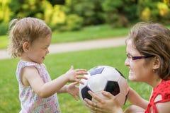 La mère et sa fille jouent avec la boule du football en parc Photographie stock