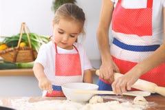 La mère et sa fille mignonne prépare la pâte à la table en bois Pâtisserie faite maison pour le pain ou la pizza Fond de boulange Images stock