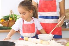 La mère et sa fille mignonne prépare la pâte à la table en bois Pâtisserie faite maison pour le pain ou la pizza Fond de boulange Photographie stock