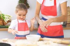 La mère et sa fille mignonne prépare la pâte à la table en bois Pâtisserie faite maison pour le pain ou la pizza Fond de boulange Photo libre de droits