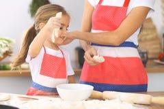 La mère et sa fille mignonne prépare la pâte à la table en bois Pâtisserie faite maison pour le pain ou la pizza Fond de boulange Photographie stock libre de droits