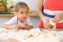 La mère et sa fille mignonne prépare la pâte à la table en bois Pâtisserie faite maison pour le pain ou la pizza Fond de boulange Photo stock