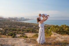 La mère et son fils ont l'amusement à la plage de mer au coucher du soleil Image stock