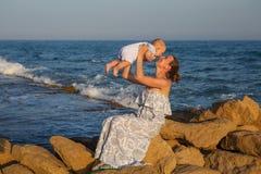 La mère et son fils ont l'amusement à la plage de mer au coucher du soleil Images stock