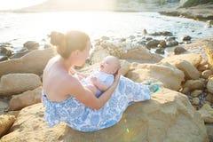 La mère et son fils ont l'amusement à la plage de mer au coucher du soleil Photographie stock libre de droits
