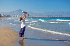 La mère et son fils ont l'amusement à la plage de mer au coucher du soleil Images libres de droits