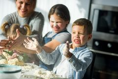 La mère et trois enfants préparent quelque chose de la pâte Photos stock