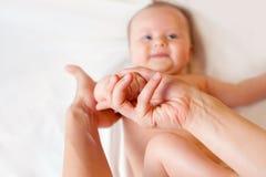 La mère fait le massage de doigt pour le bébé Photographie stock