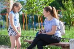 La mère fait sauter sa jeune fille pour le mauvais comportement tout en marchant sur le terrain de jeu photo libre de droits