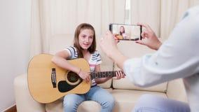 La mère fait une vidéo de sa jeune fille jouant sur une guitare acoustique banque de vidéos