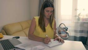 La mère fatiguée écrit le ` heureux du ` m du ` I pendant les mensonges de bébé dans le berceau banque de vidéos
