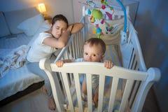 La mère fatiguée est devenue endormie à côté de la huche du ` s de bébé Images libres de droits