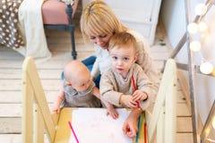 La mère forme les petits enfants pour écrire et dessiner Image libre de droits