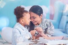 La mère gaie et la fille positives tenant un puzzle rapiècent Image stock