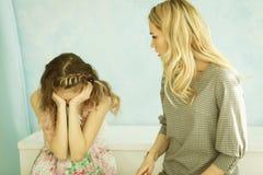 La mère gronde sa fille à la maison La fille a couvert son visage de ses mains et a abaissé sa tête photo libre de droits