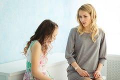 La mère gronde sa fille à la maison La fille a couvert son visage de ses mains et a abaissé sa tête images stock