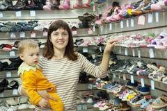 La mère heureuse avec l'enfant choisit des chaussures de chéri Images libres de droits