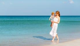 La mère heureuse de famille avec le fils de bébé marche par l'océan sur la plage en somme Photographie stock