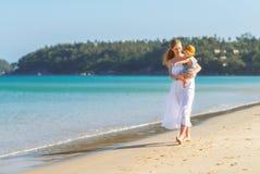 La mère heureuse de famille avec le fils de bébé marche par l'océan sur la plage en somme Image libre de droits