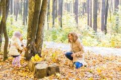 La mère heureuse de famille et la fille d'enfant jouant le jet part dans le parc d'automne dehors Photographie stock