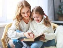 La mère heureuse de famille lit le livre à l'enfant à la fille par la fenêtre photographie stock libre de droits