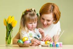 La mère heureuse enseigne la fille d'enfant à décorer des oeufs de pâques Image libre de droits