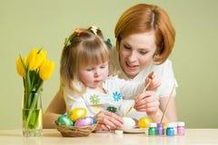 La mère heureuse enseigne la fille d'enfant à peindre des oeufs de pâques Images libres de droits